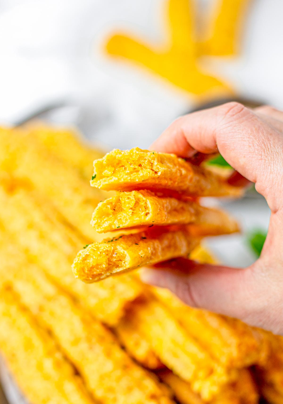 Hand holding up Cheese Straws broken in half.