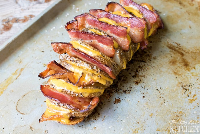 Fully Loaded Hasselback Potatoes, russet potatoes cut and baked until crispy, loaded with cheese and bacon, topped with all the fixings! from ThisSillyGirlsLife.com #JimmyDeanBacon #ad