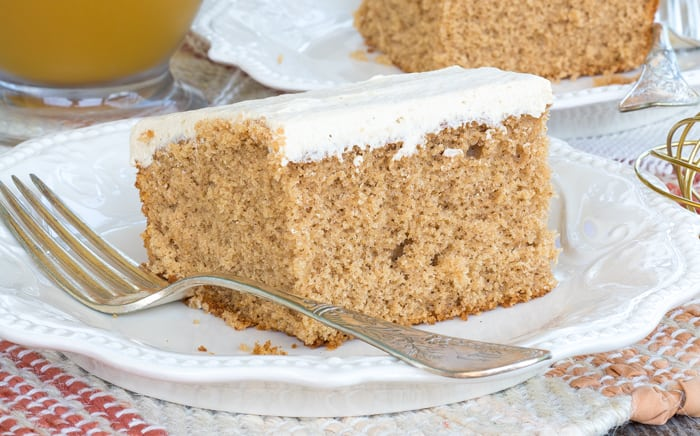 Close up of one slice of Spiced Apple Cider Sheet Cake on white plate with fork.