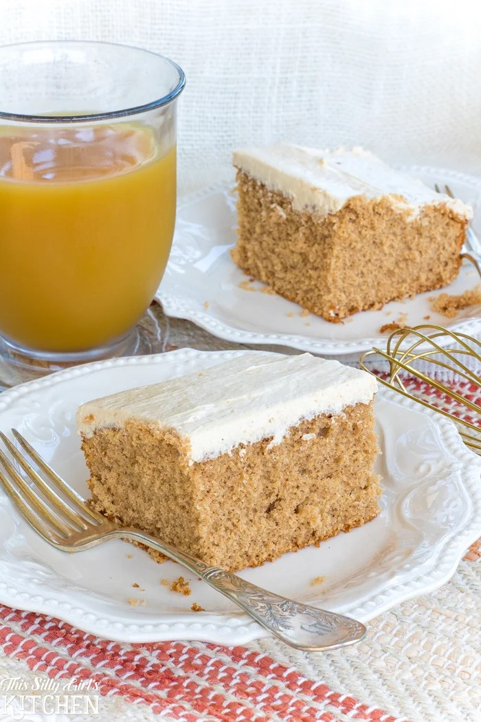 Slices of sheet cake on plates with forks with a glass of apple cider in background.