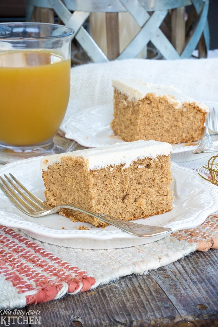 Spiced Apple Cider Sheet Cake slices on white plate with apple cider in background.