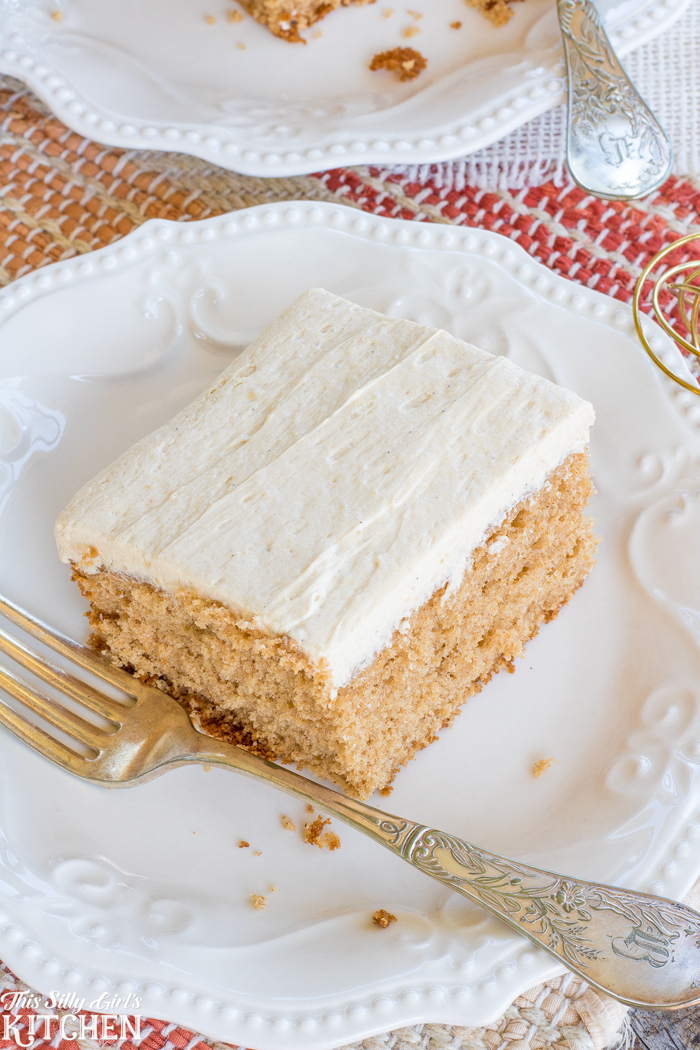 Overhead of frosted Spiced Apple Cider Sheet Cake on white plate showing frosting.