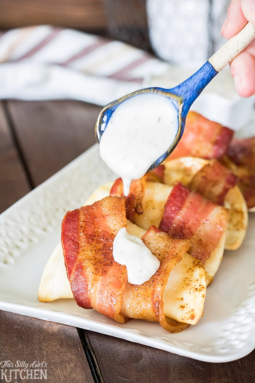 Sweet and Spicy Bacon Wrapped Pierogies, cheesy pierogies wrapped in bacon and baked until crispy. Recipe from ThisSillyGirlsKitchen.com