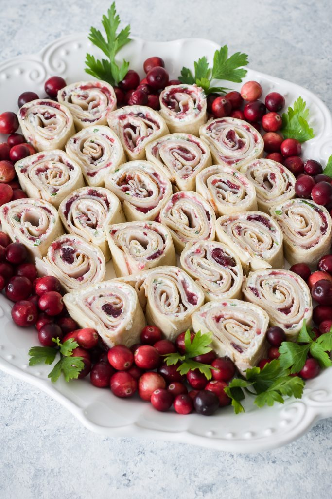 Cranberry Turkey Pinwheels on serving tray with whole cranberries and parsley