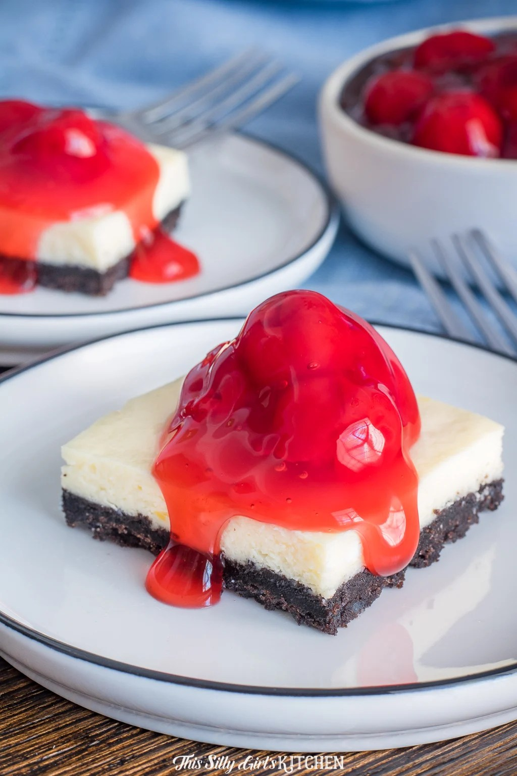 Two Cheesecake bars on white plate topped with cherry pie filling