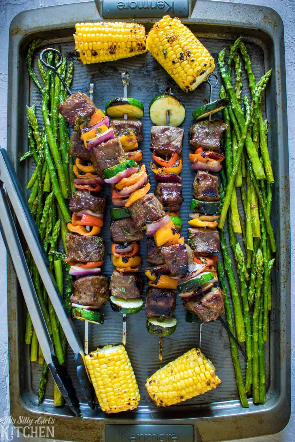 Carne Asada Steak Kabobs with corn and asparagus on baking pan.