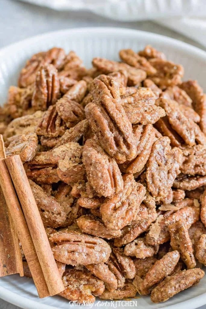 Close up of Pecans in white bowl with cinnamon sticks