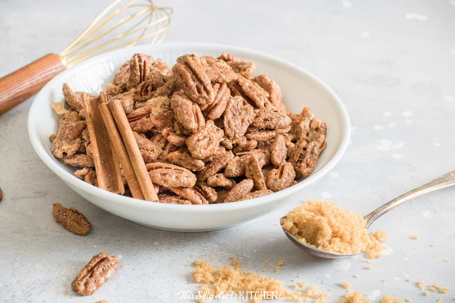 Horizontal photo of pecan sin white bowl with whisk and spoon of brown sugar