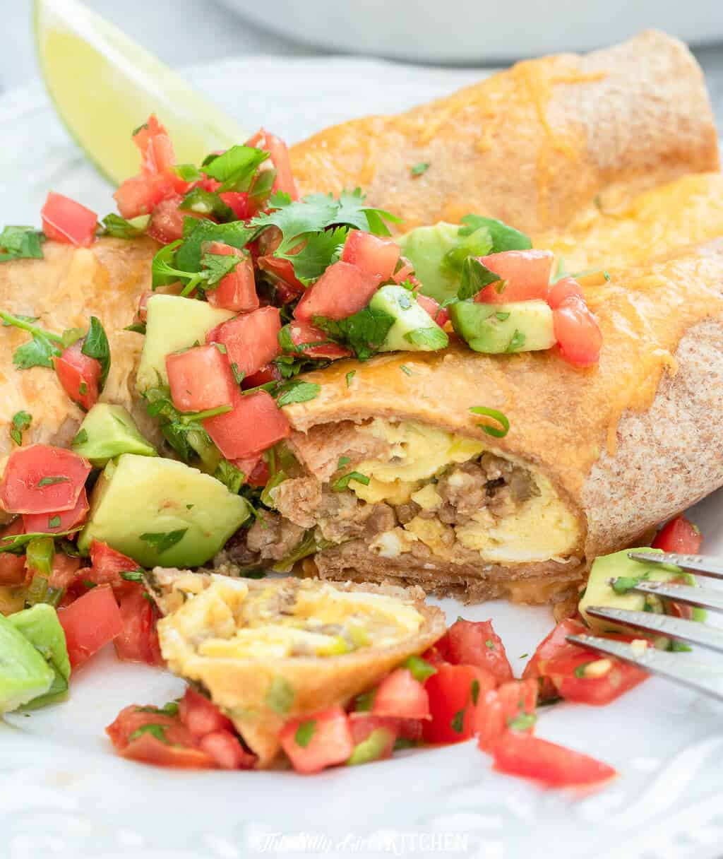 With Mexican flavors, ground beef, eggs, and a luscious cheese sauce these breakfast enchiladas are a crowd pleaser! #recipe from thissillygirlskitchen.com #breakfast #enchiladas #breakfastenchiladas #Mexican