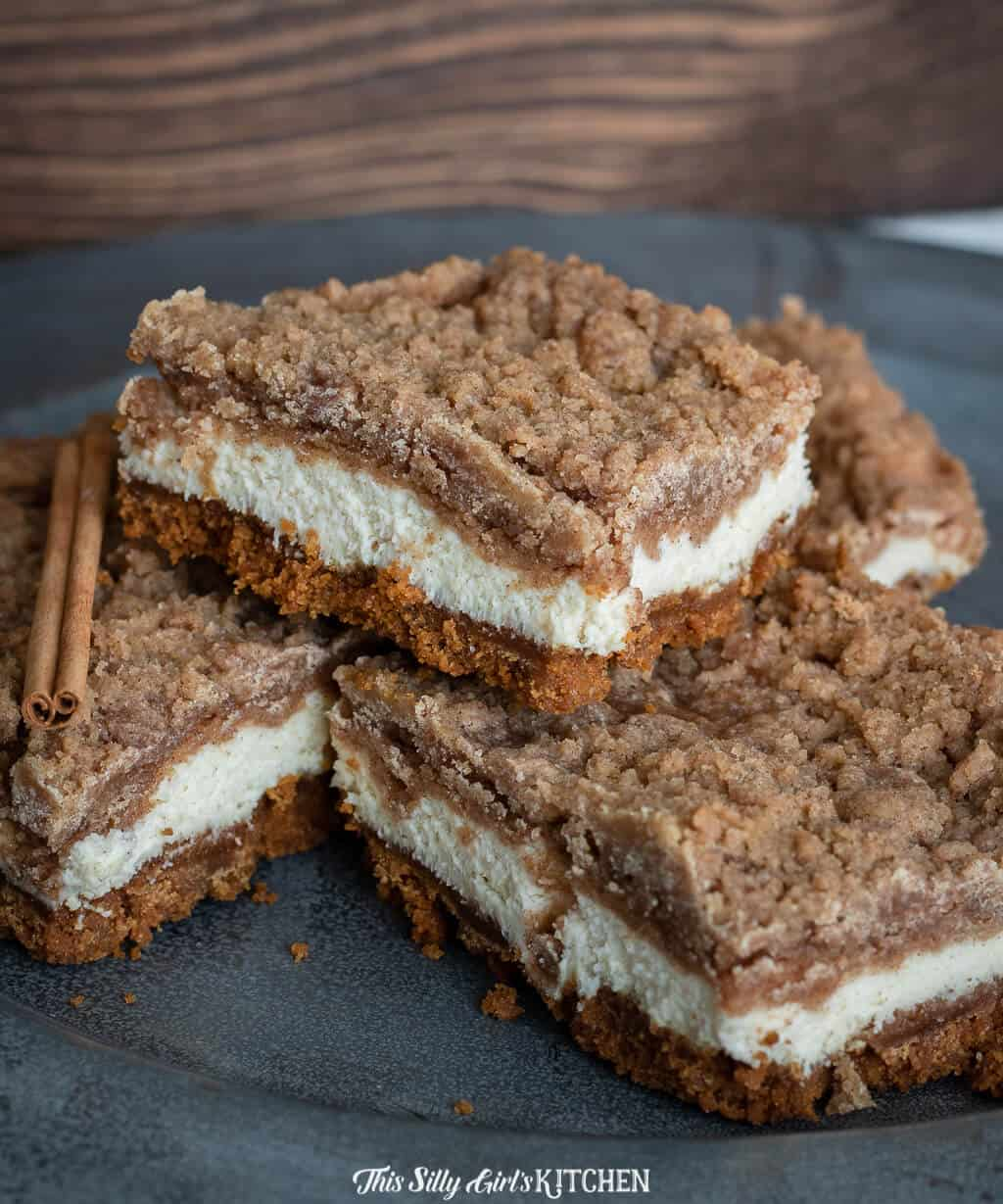 Snickerdoodle Bars stacked on top of one another on black plate.