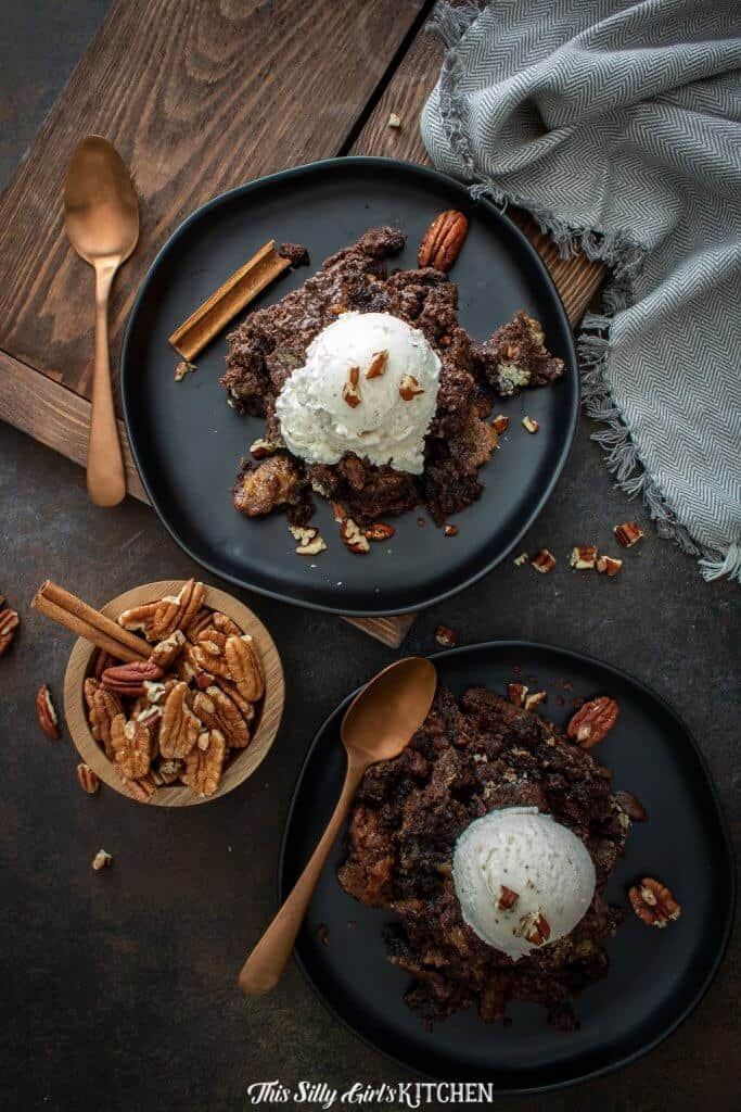 Overhead of cobbler on black plates topped with ice cream and pecans