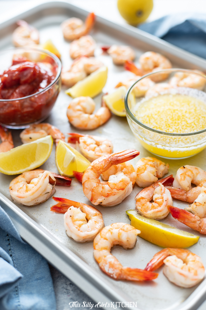 Butter and cocktail sauce on baking sheet with shrimp and lemon wedges
