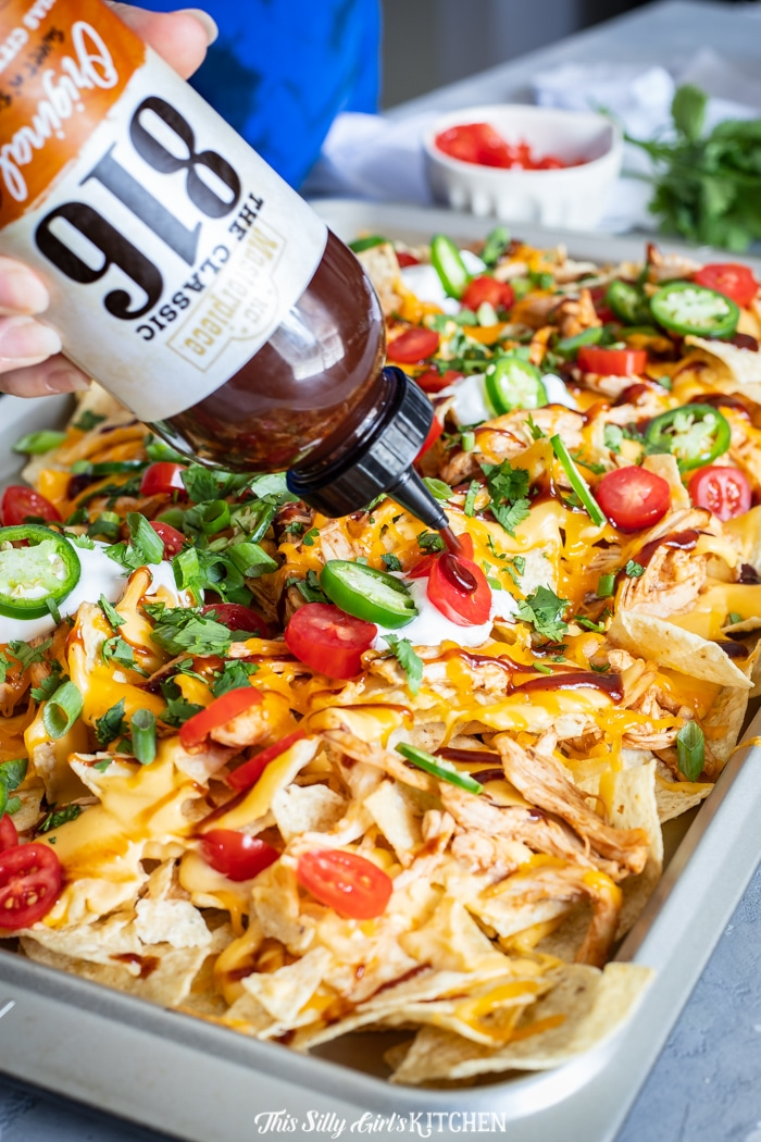 BBQ Sauce being drizzled over Nachos on pan