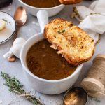 Finished French Onion Soup in white bowl with bread square image