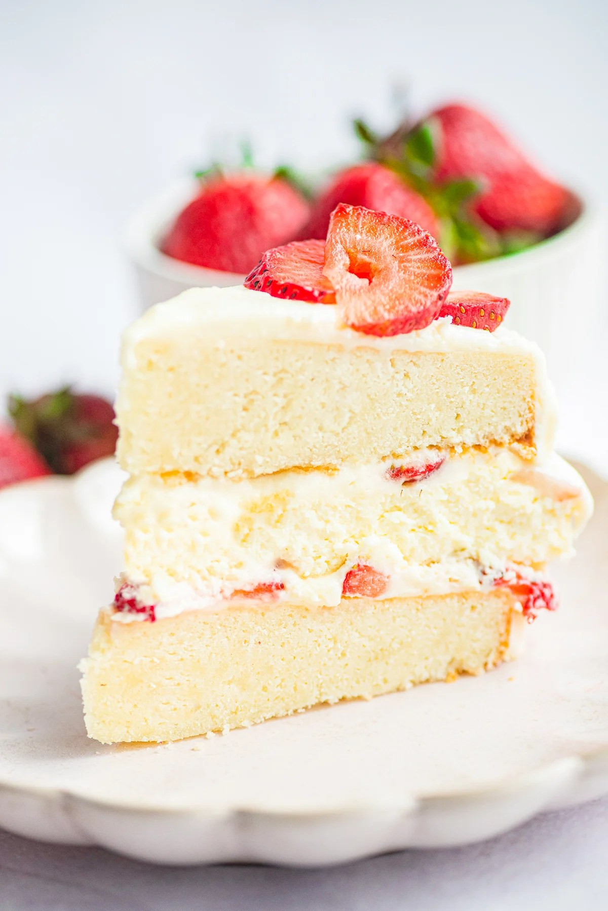 Slice of cake on white plate showing each layers topped with strawberries