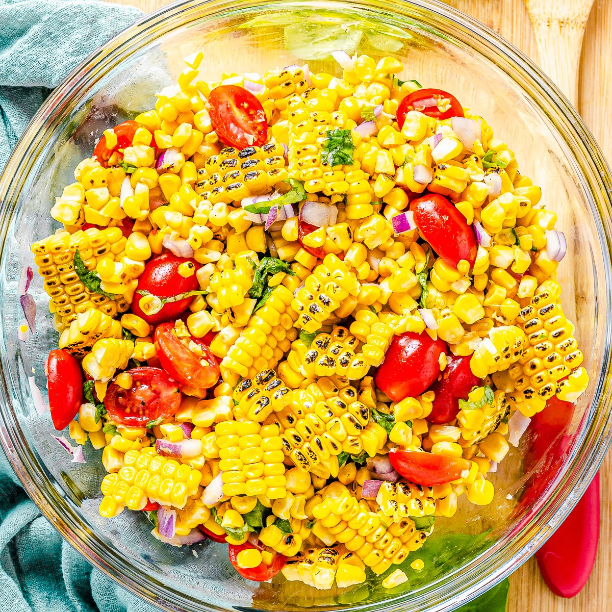 Square image of Corn and Tomato Salad overhead in clear bowl