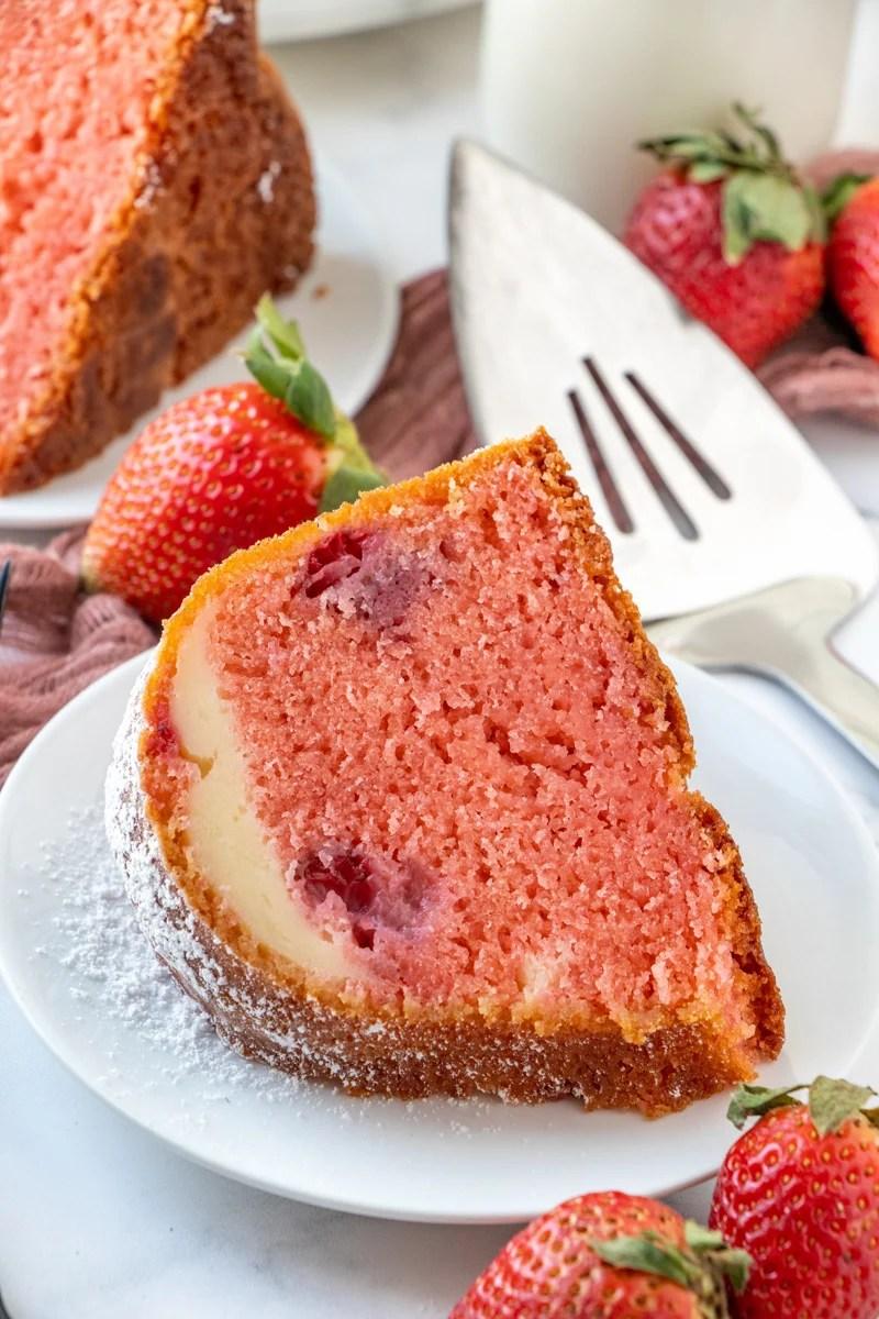 Slice of Strawberry Cheesecake Bundt Cake on white plate showing cheesecake ribbon