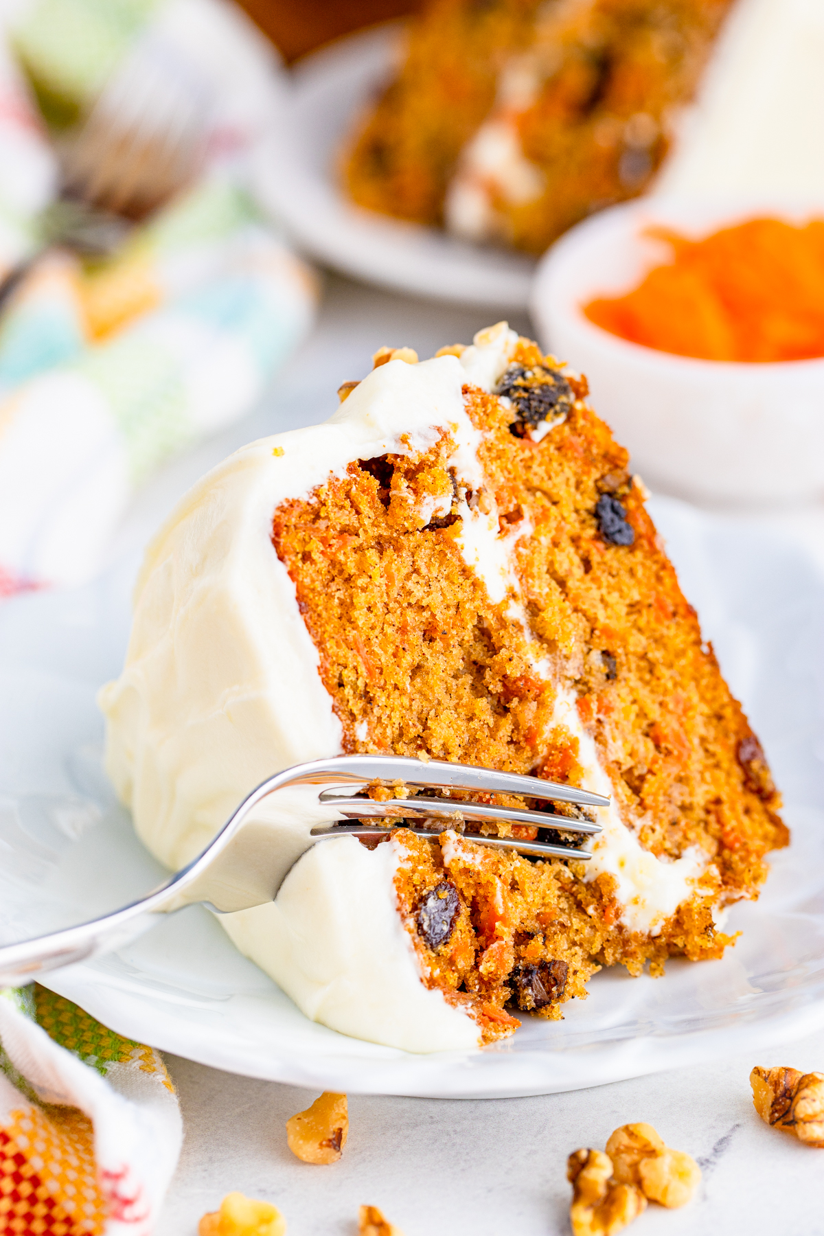 Fork cutting into slice of Layered Carrot Cake