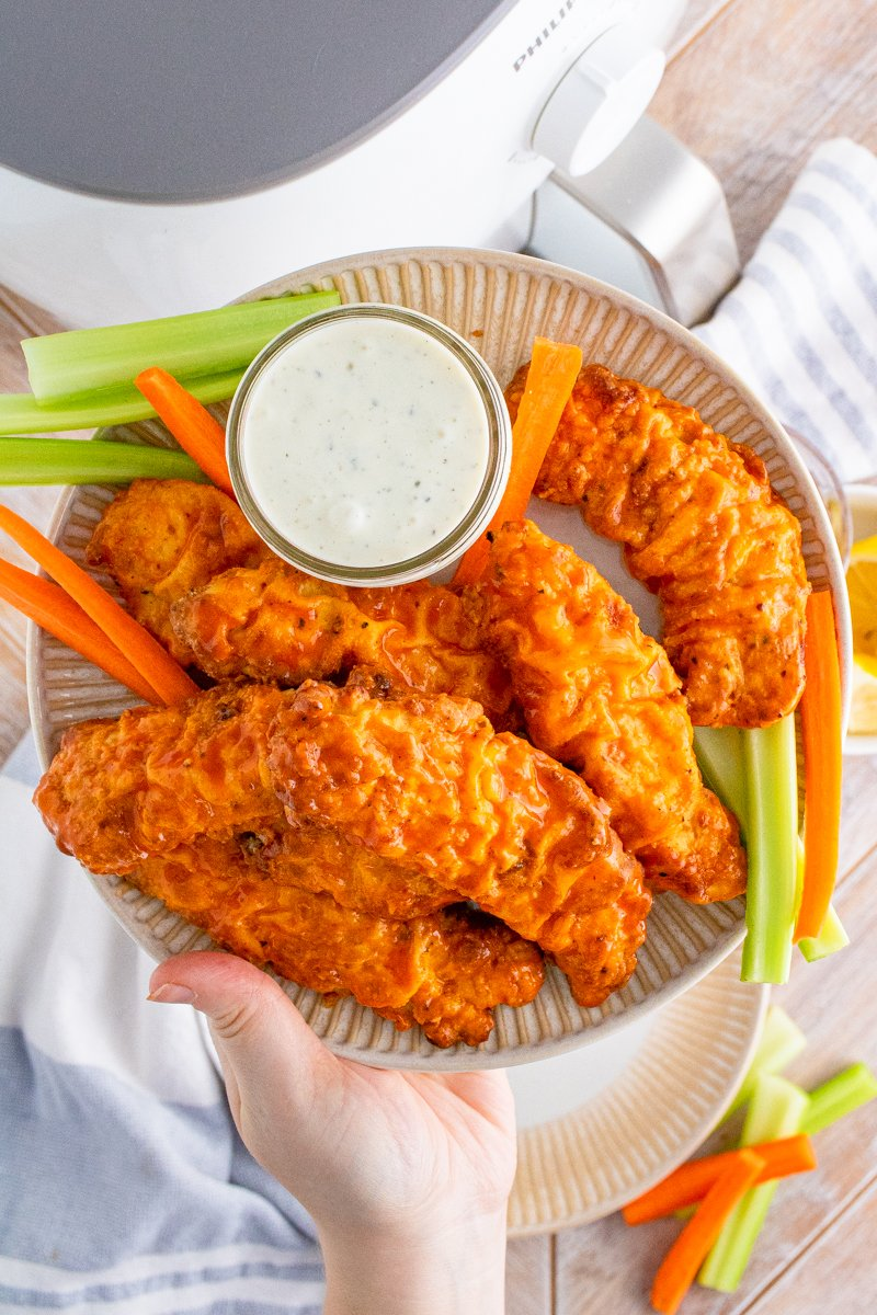 Hand holding up plate full of Buffalo Chicken Tenders