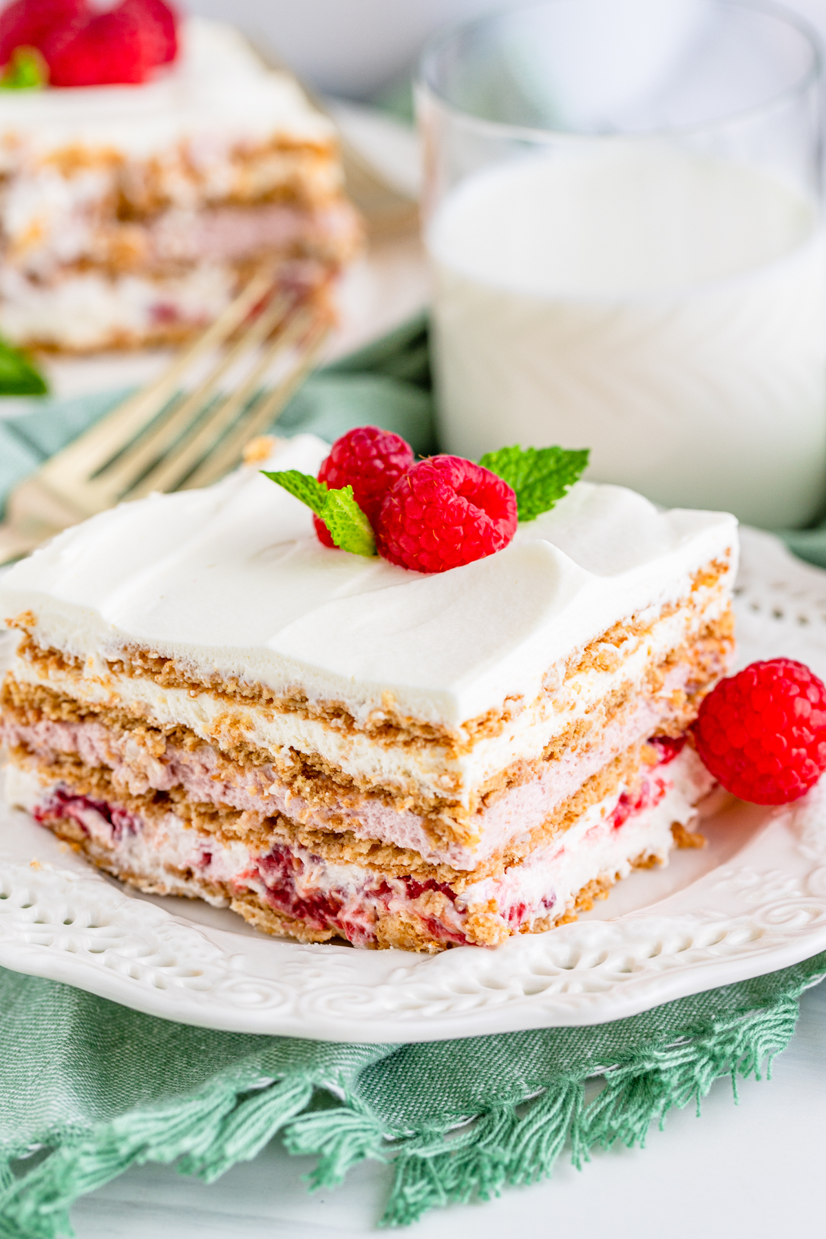 Slice of Raspberry Icebox Cake slice on white plate topped with raspberries and mint