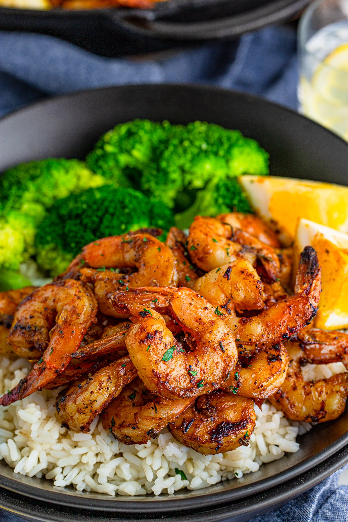 Blackened Shrimp over rice on plate with broccoli and lemon