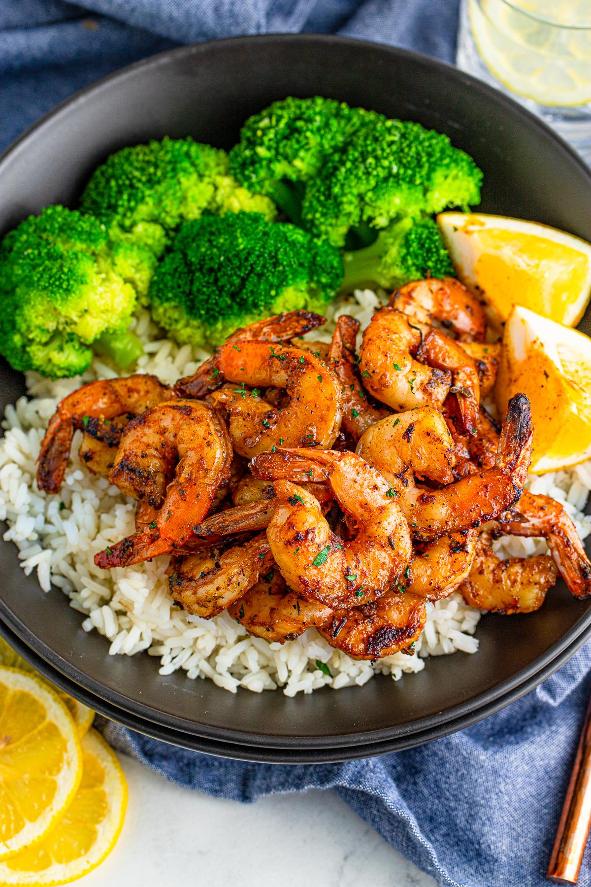 Shrimp overhead photo on black plate with rice and broccoili