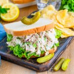 Square photo of Tuna Salad Sandwich with chips topped with a pickle