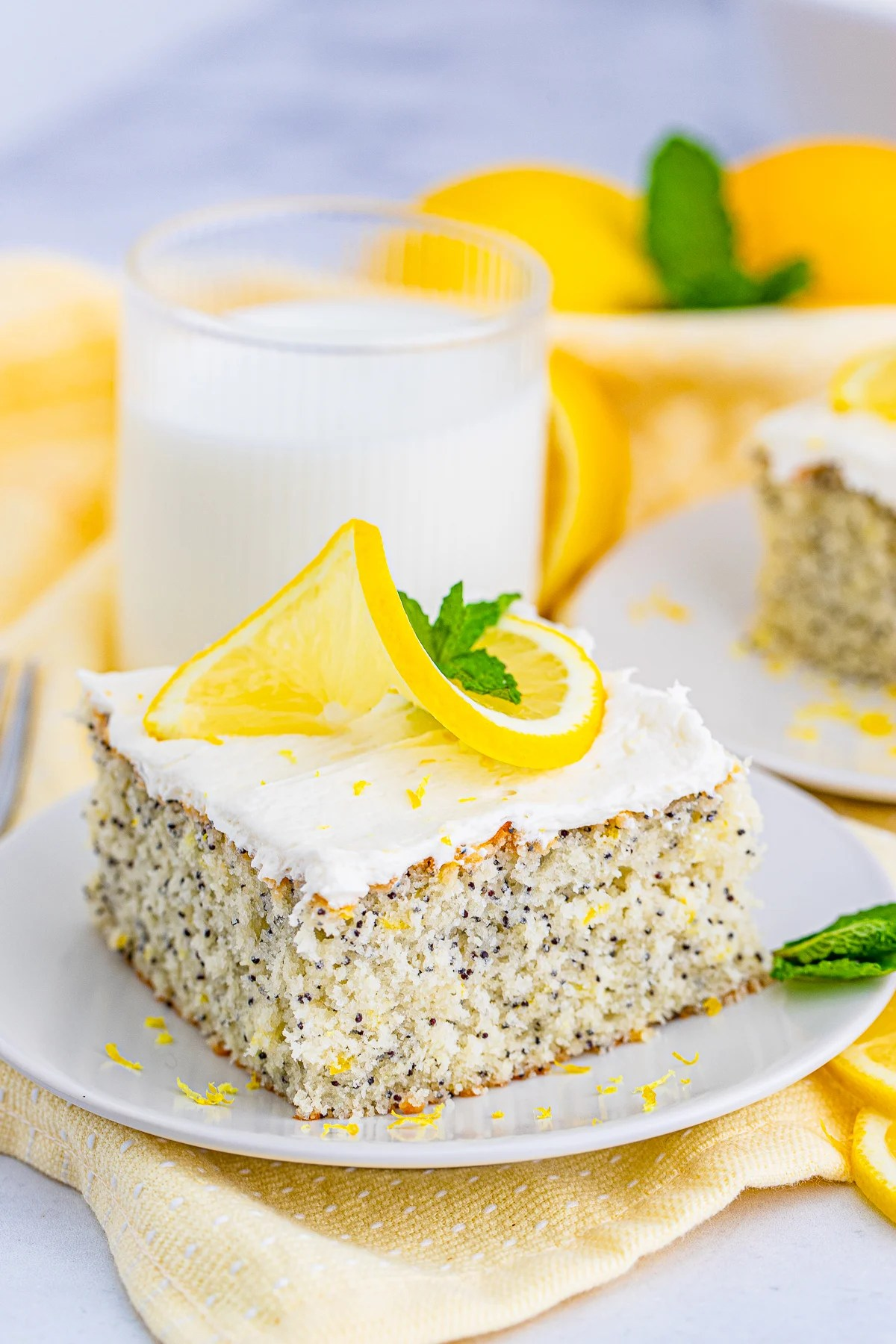 Lemon Poppy Seed Cake slice on white plate topped with lemon and mint
