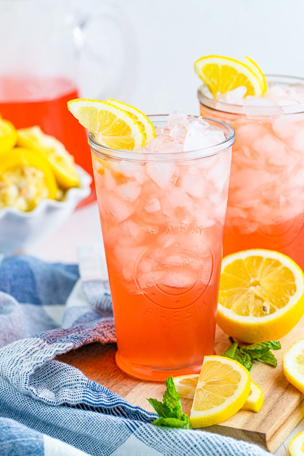 Two glasses of Pink Lemonade Recipe with lemons and mint