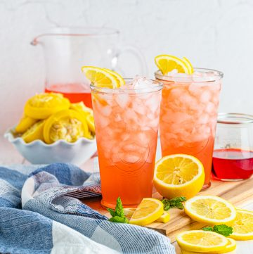 Square image to two glasses of Pink Lemonade with lemons as garnish