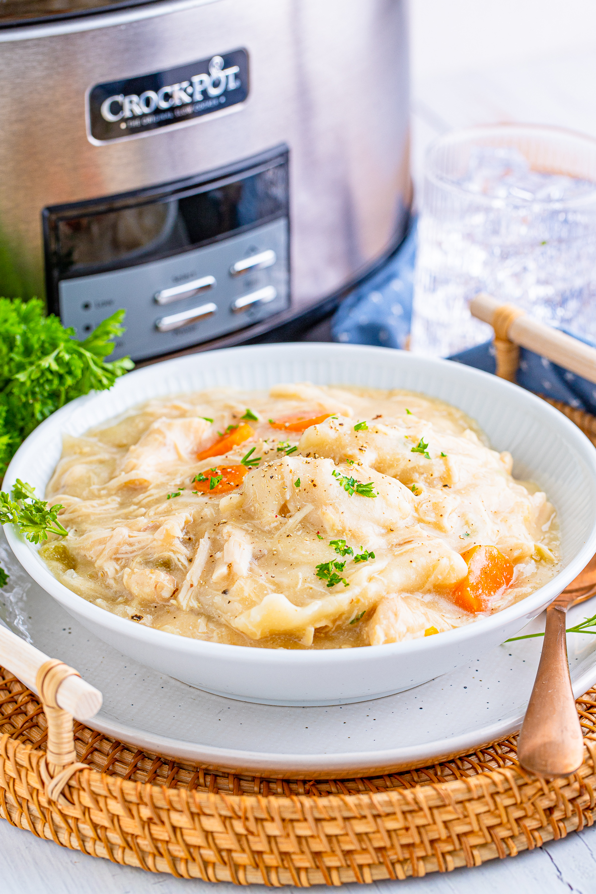 Slow Cooker Chicken and Dumplings in white bowl in front of slow cooker.