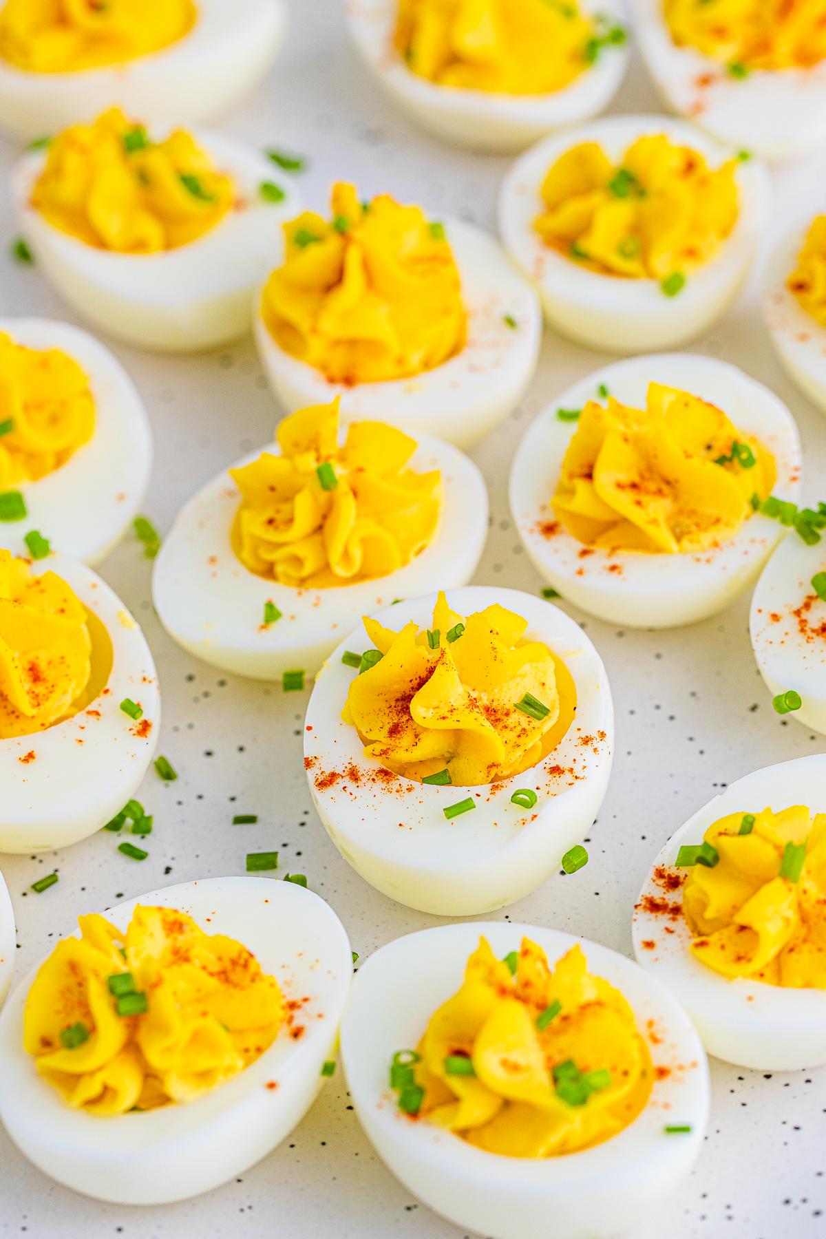 Close up of garnished eggs on white platter.