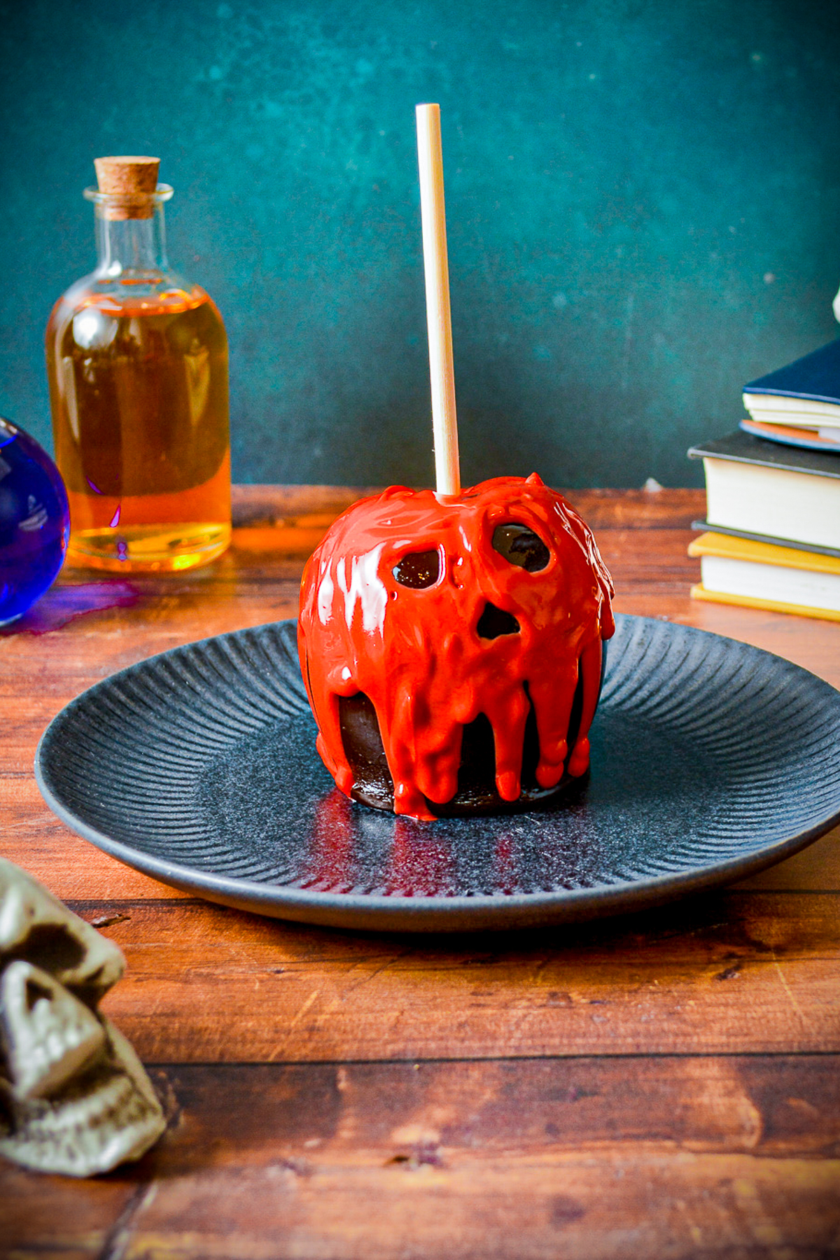 Poison Apple finished on plate with books in back and skull in front.