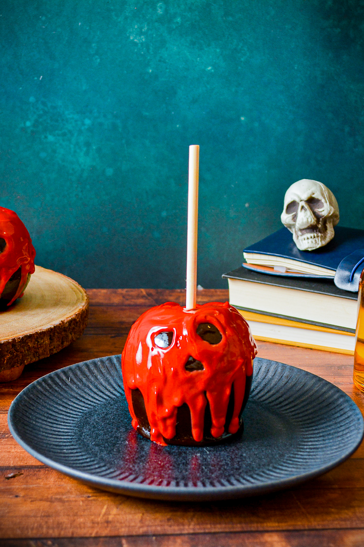 One Poison Apple on plate with books and skull in background.