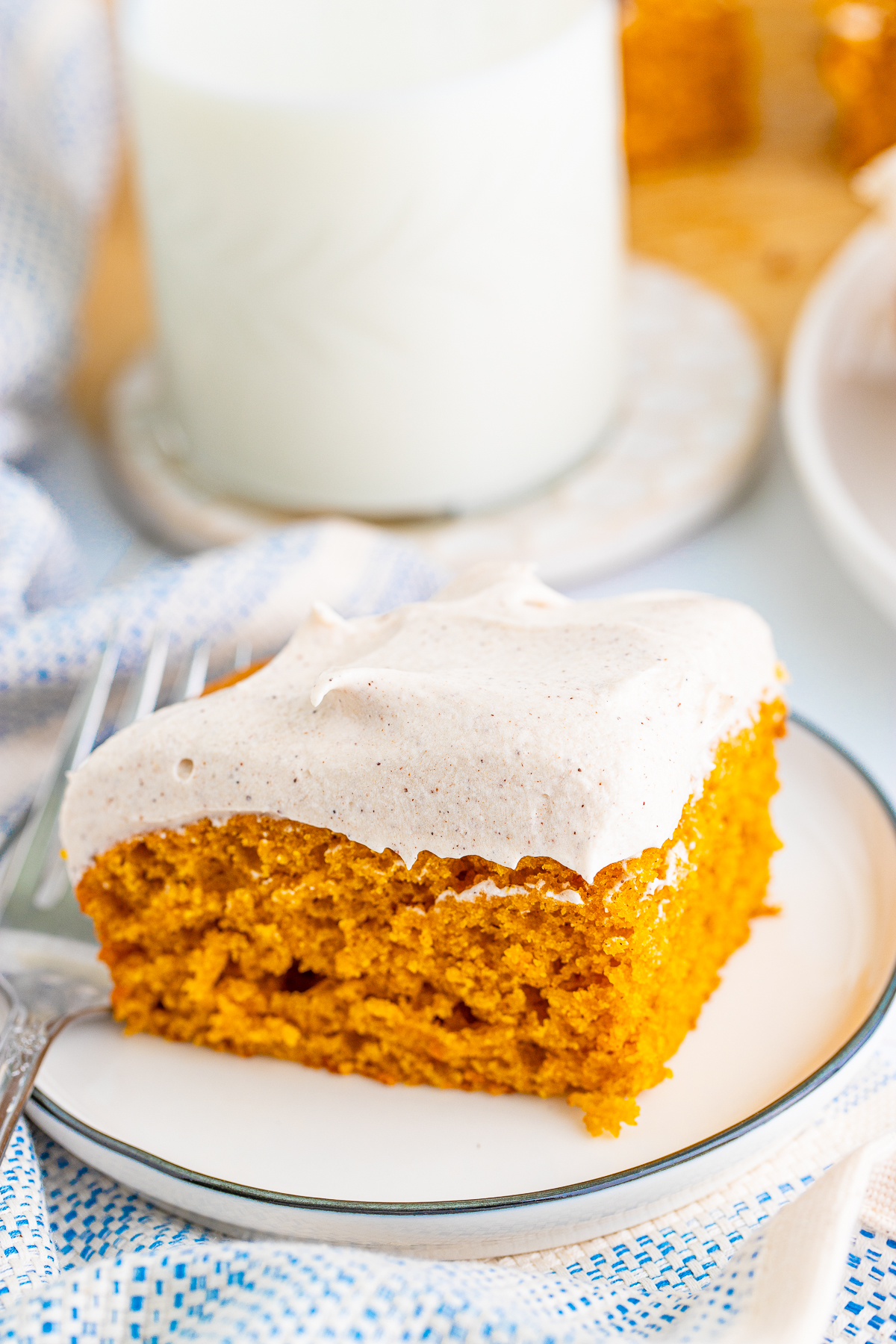 Cut Pumpkin Bar Recipe slice on white plate frosted.
