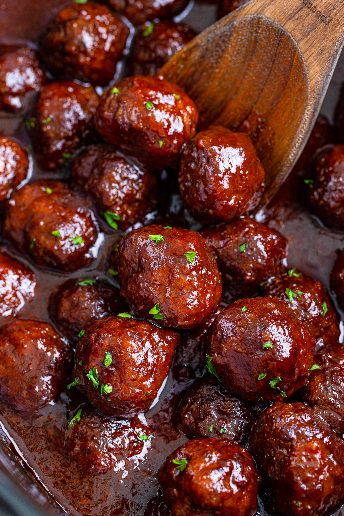 Close up of Grape Jelly Meatballs in Crock Pot with wooden spoon