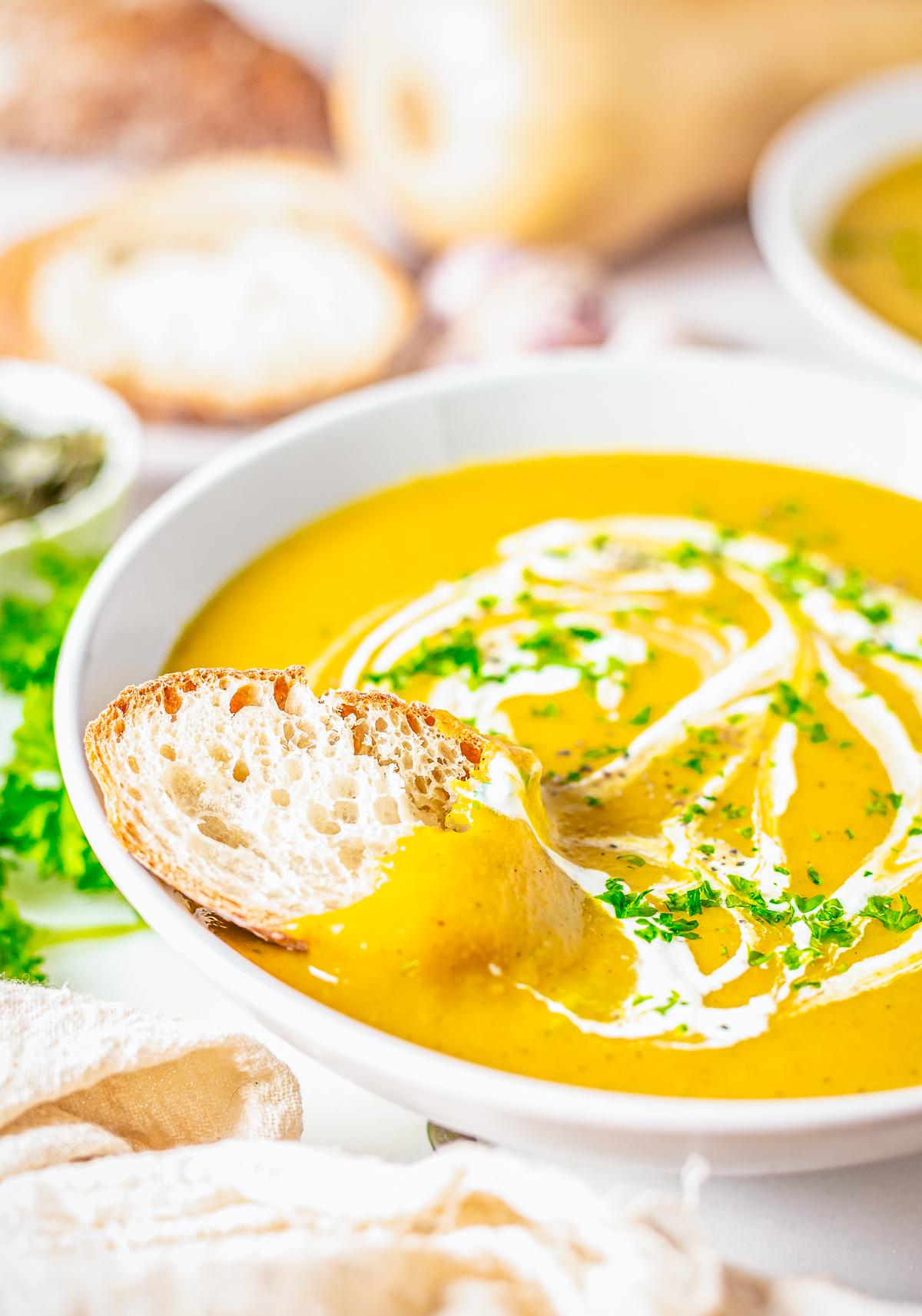 Bread in bowl of The Best Butternut Squash Soup Recipe.