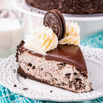 Square image of slice of cheesecake on white plate with whipped cream and Oreo.