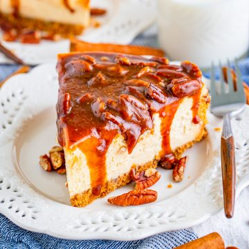 Square image of cheesecake on plate with topping dripping down sides.