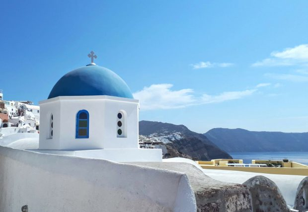 White church with blue dome against blue sky background