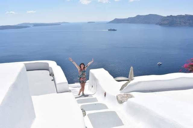Woman standing on white path in front of oia caldera with arms in the air