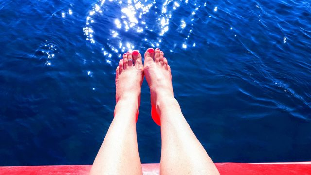 Bare legs on the side of a boat with pink toenails against a blue sea backdrop