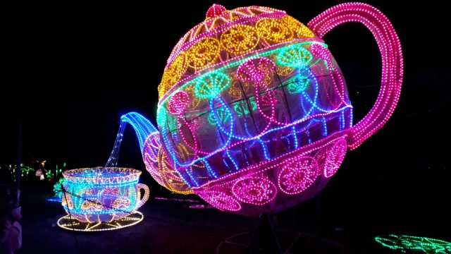 Multicoloured teapot pouring into teacup