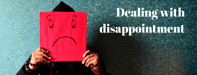 Person holding picture in front of their face showing a drawing of a sad face. Text: dealing with disappointment