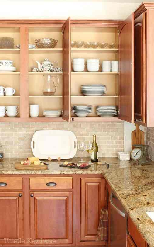 Organized kitchen cabinet with white dishes.