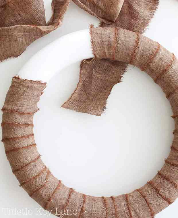 Wrap a foam wreath form with strips of fabric.