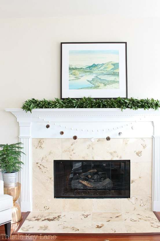 Christmas mantel with bay leaf garland and pinecones.