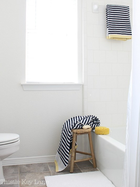 Simple accessories and a stool next to the tub.