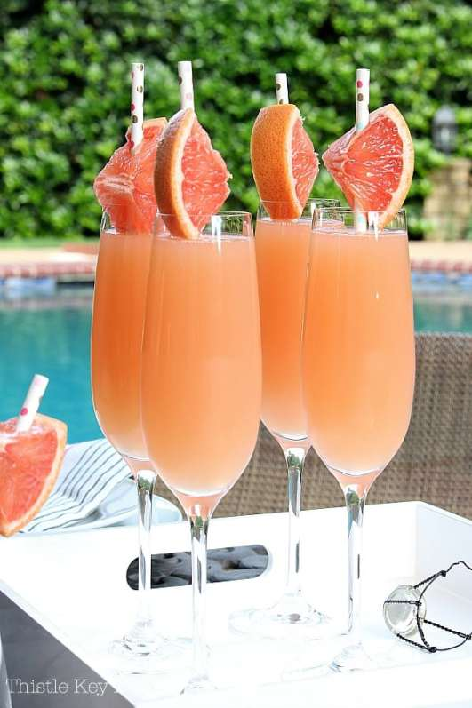 Grapefruit wedges on straws used as a garnish for Grapefruit Mimosas.