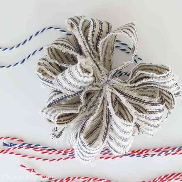 Rag bow made with strips of blue ticking fabric.